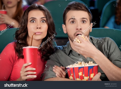 stock-photo-exciting-movie-shocked-young-couple-eating-popcorn-and-drinking-soda-while-watching-movie-at-the-148169351